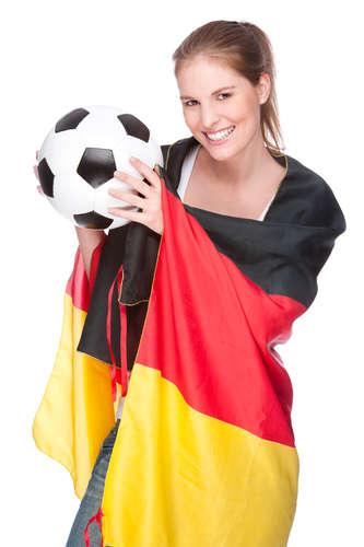 Junge, schöne Frau mit Fußball und Deutschland-Flagge