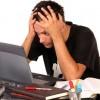 Stressed young man studies laptop / Gestresster junger Mann vor einem Laptop