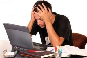 Gestresster junger Mann vor einem Laptop