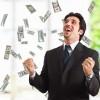 Businessman stands under shower of bank notes / Geschäftsmann steht unter einer Dusche von Banknoten