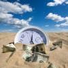 Clock and Dollars half buried in desert sand / Uhr und Dollarscheine zur Hälfte im Wüstensand begraben