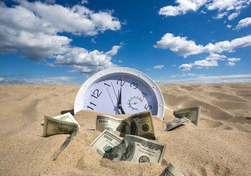 Uhr und Dollarscheine zur Hälfte im Wüstensand begraben