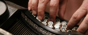 Hände schreiben einen Text auf einer alten Schreibmaschine