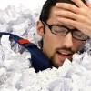 Man with calculator sunk into a heap of paper / Mann mit Taschenrechner versenkt in einem Papierhaufen