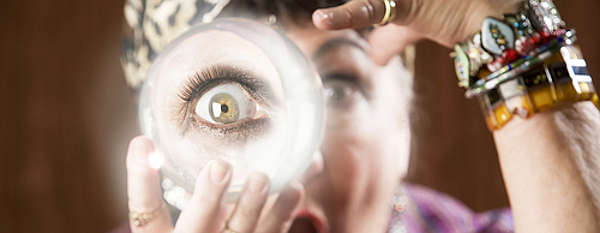 Female fortune teller holding a crystal ball to her eye / Wahrsagerin hält eine Kristallkugel am Auge