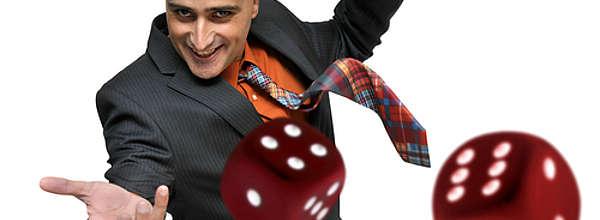 Grinsender Mann in einem Anzug wirft rote Würfel