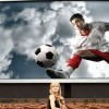 Solitary woman in front of a giant soccer screen / Einsame Frau vor einem riesigen Bildschirm mit Fußballspieler