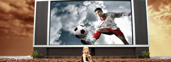 Einsame Frau vor einem riesigen Bildschirm mit Fußballspieler