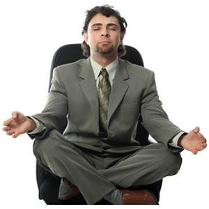 Mann sitzt im Schneidersitz auf einem Stuhl mit geschlossenen Augen in einer Beschwörungsstellung