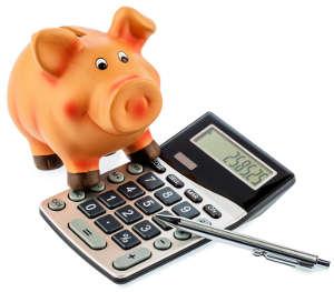 Roter Stift auf einem Taschenrechner neben einem Sparschwein - Kosten sparen und Ausgaben reduzieren