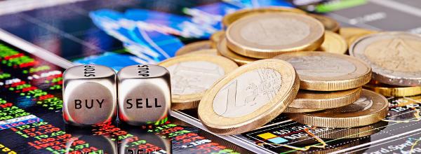 Dices cubes with the words SELL and BUY, Euro coins and a financial chart / Würfel mit den Worten Kaufen und Verkaufen, Euro-Münzen und Chart