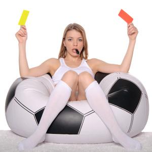Sexy Frau sitzt auf einem großen Fußball mit roten und gelben Karten