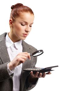 Porträt einer jungen Geschäftsfrau mit Rechner und Lupe